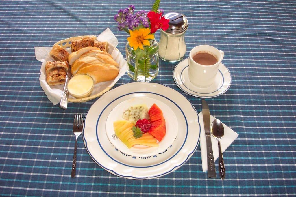 El desayuno incluye un plato de frutas, huevos con chilaquiles u otros, pan, y café o té.
