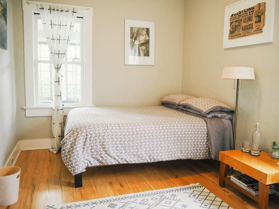 Clean and cozy private bedroom with full bed, lots of light, a closet, and an adjacent semi-private bathroom.