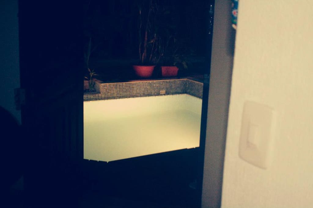 view from inside the house to the pool at night