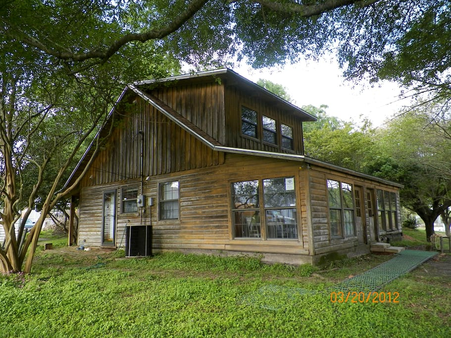 Bayou side view of Log Cabin. Your bedroom with private bath is upstairs, with view to Bayou Teche.
