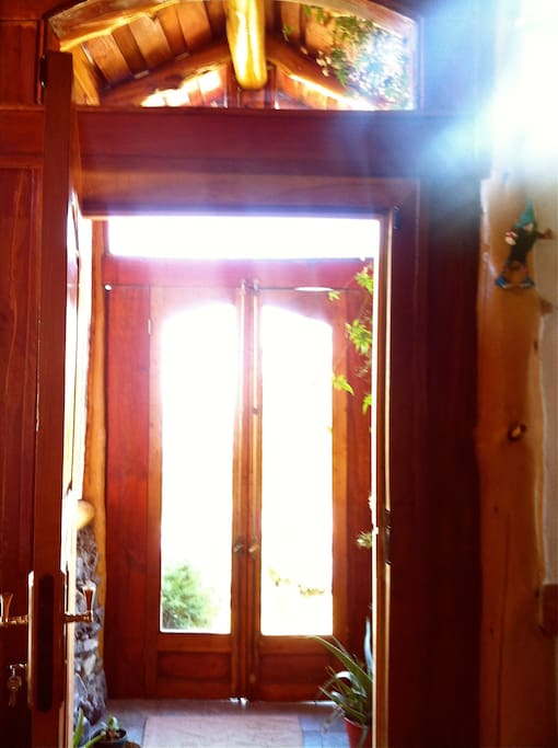 One of the entrance is a sunlight spot , notice the volcano rocks, native wood and a jazmin plant climbing the window)