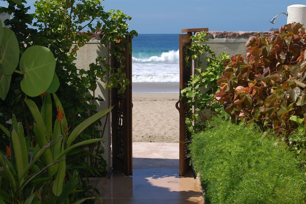 Gate leading out to the beach.  Relax under our palapas and lounge chairs.