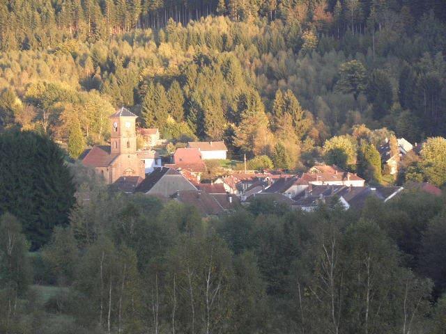 Vue du village dans la vallée, entouré de 2 chaînes de montagnes vosgiennes