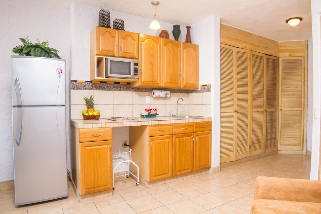 Kitchenette with a small microwave oven and a mid size fridge, closet on the right has a security box.
