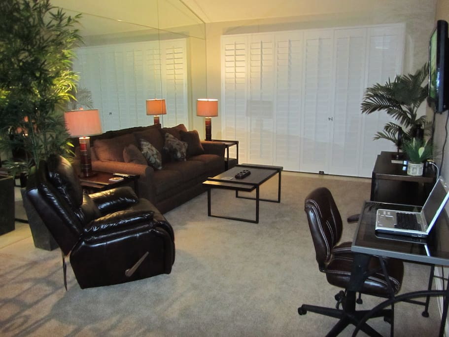 Living room with flat screen and computer work area.