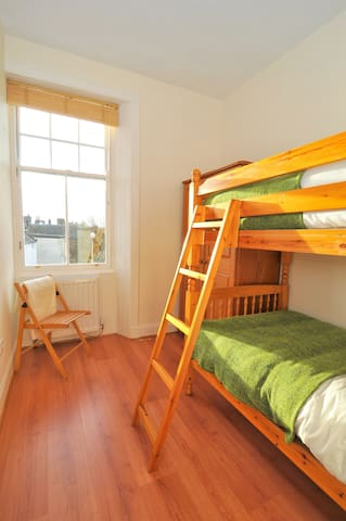 Full-size bunk beds in a bright, cosy room.