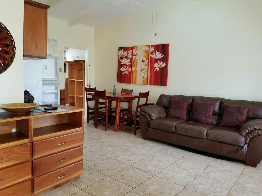 Spacious living room with large comfy couch, custom wood table, beautiful artwork and air-conditioning