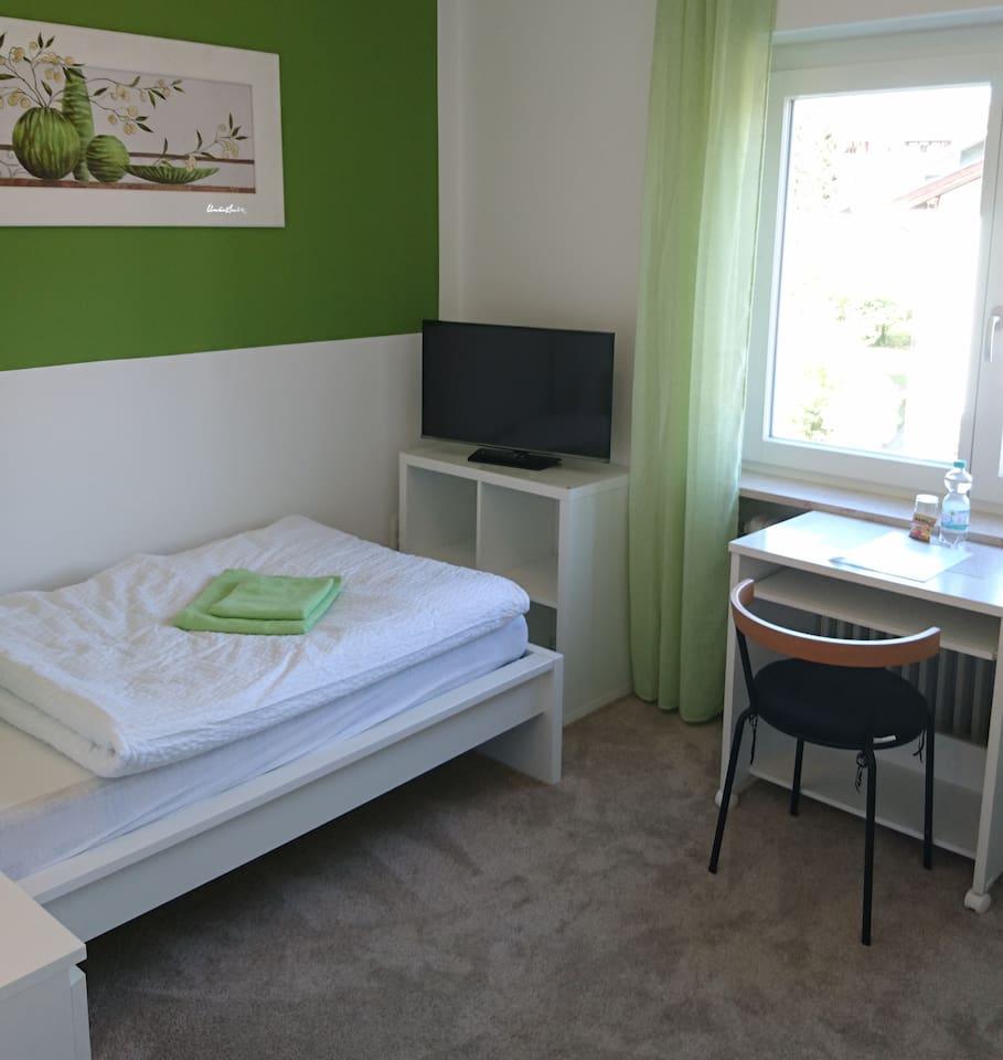 """Helles, gemütliches Einzelzimmer mit 32"""" LED TV, Schreib- / Esstisch und großen Einbauschrank."""