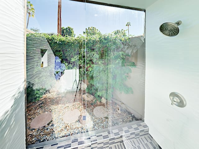 Bringing the outdoors in, the luxe walk-in shower features a huge window overlooking a completely secluded courtyard.