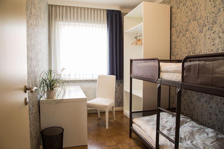Zimmer mit Hochbett und Schreibtisch