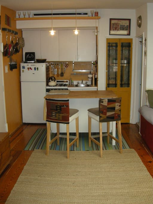 Full stocked kitchen with Butcher block table and bar stools.