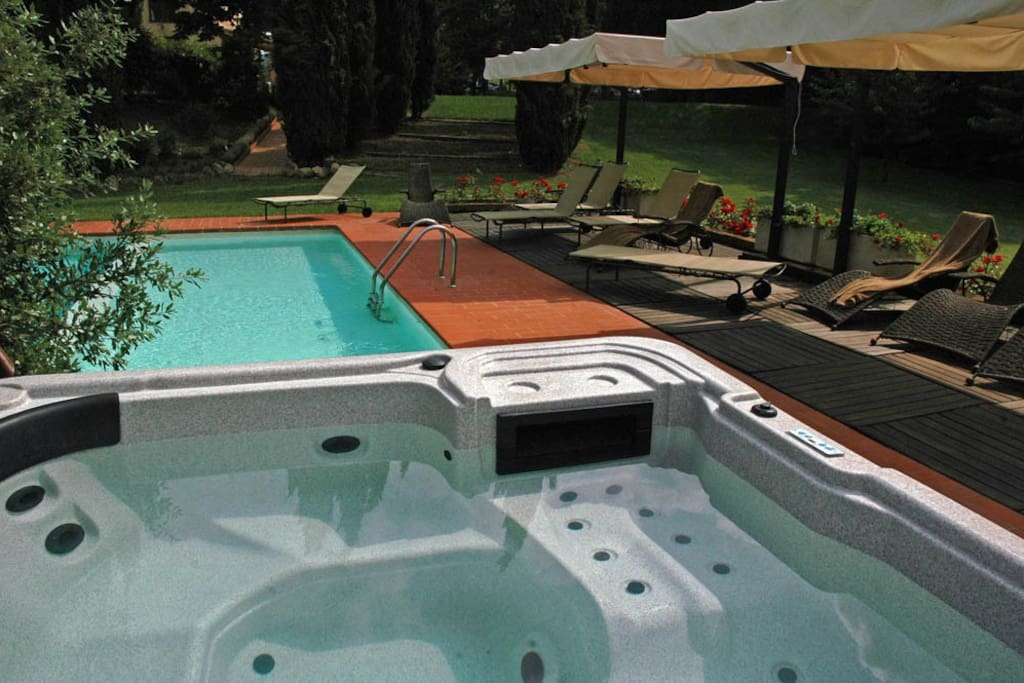 The hot tub aside the L shaped pool with a shallow end for children