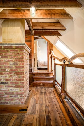 Left to the master bedroom, right to the loft on a floor of old hickory. A tree we cut down makes a railing and brick from a 100 year old building clads the chimney.