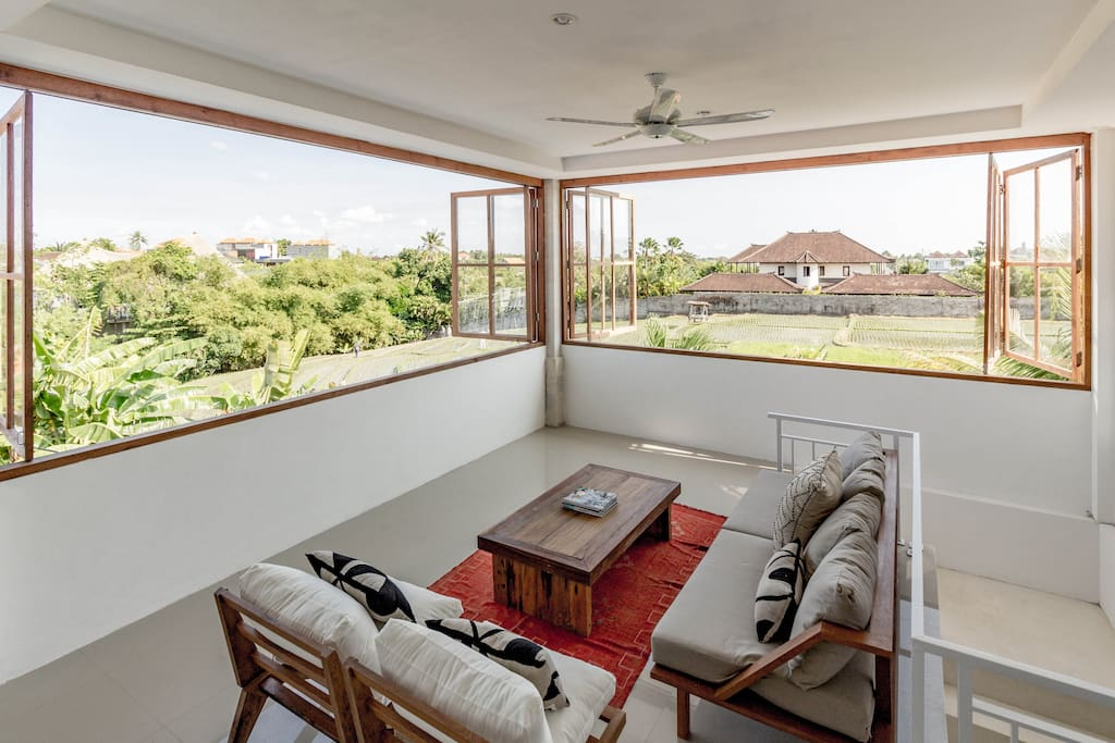 Upstairs living room with massive windows and view of rice fields