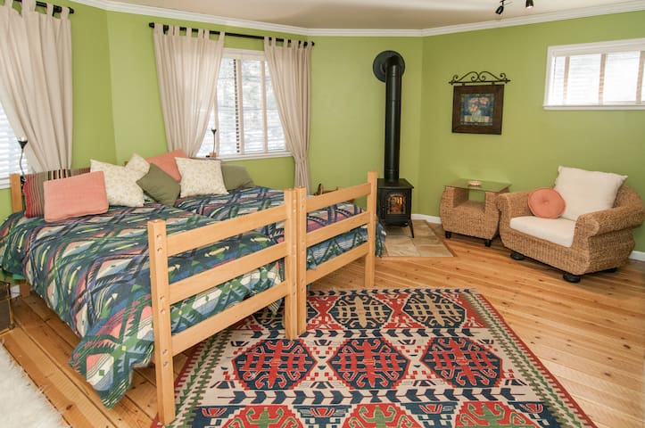 4 beds in large room with woodstove