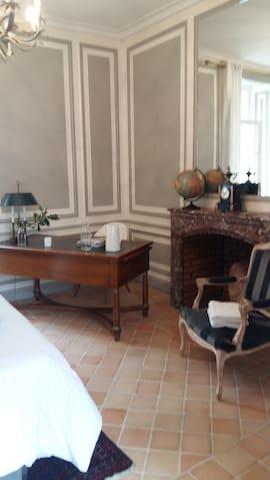 Chambre avec cheminée et bureau offrant un confort chaleureux