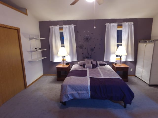 Large Master Bedroom with comfort foam mattress and bedding. High ceilings and a flat screen TV.