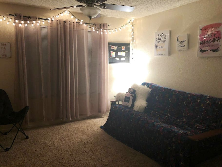 Living room/AKA your guest space! Futon that folds out into a bed, sheets and pillows provided. Ceiling fan/AC or Heat. String lights to make your stay feel cozy. My bedroom door closes and lets you stay in here privately. :)