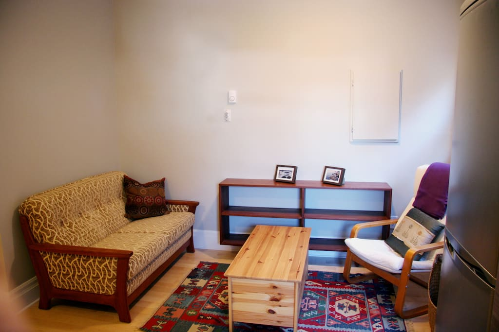 The living area is comfortably furnished with some mid-century modern teak finds and a colourful kilim rug from Turkey.