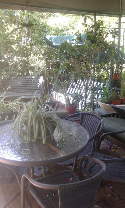 terraza con silla balancin, y sillones y mesa con 6 sillas y dos sillones.