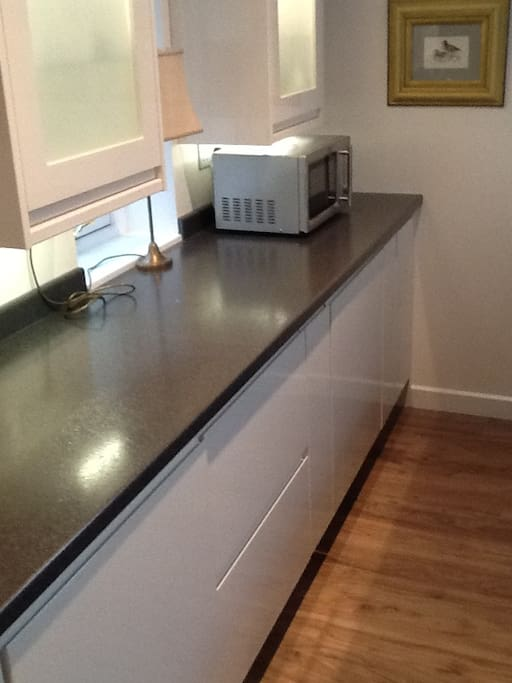 Spacious kitchen work bench with microwave and ample storage cupboards and drawers