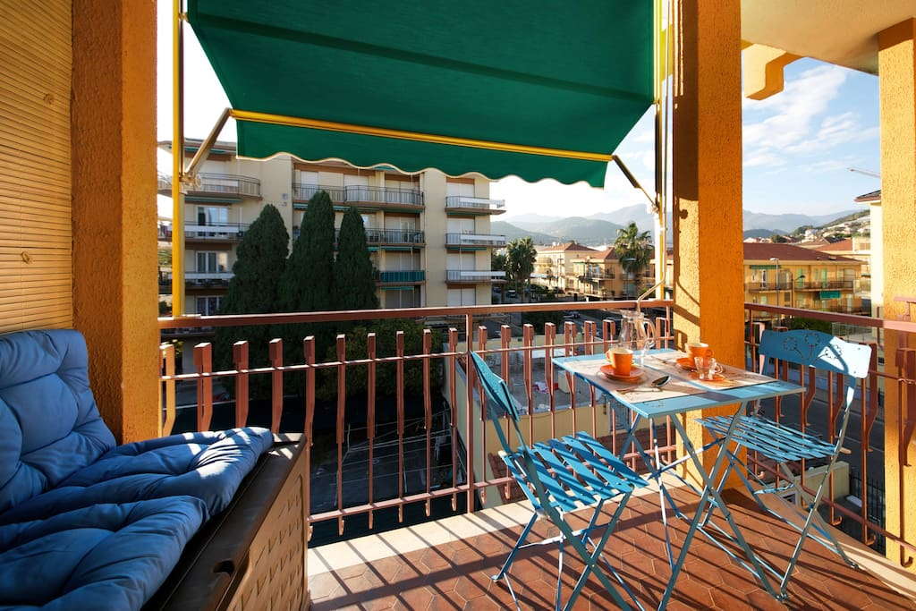 Balcony with chairs, table and awning