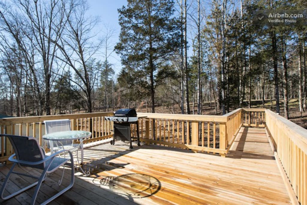 Private deck with grill and outdoor sitting.