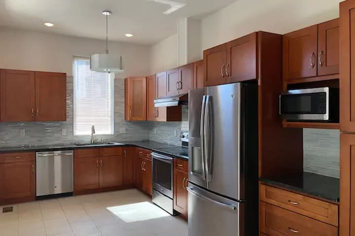 Fully equipped kitchen with fridge, microwave, range, and cookware