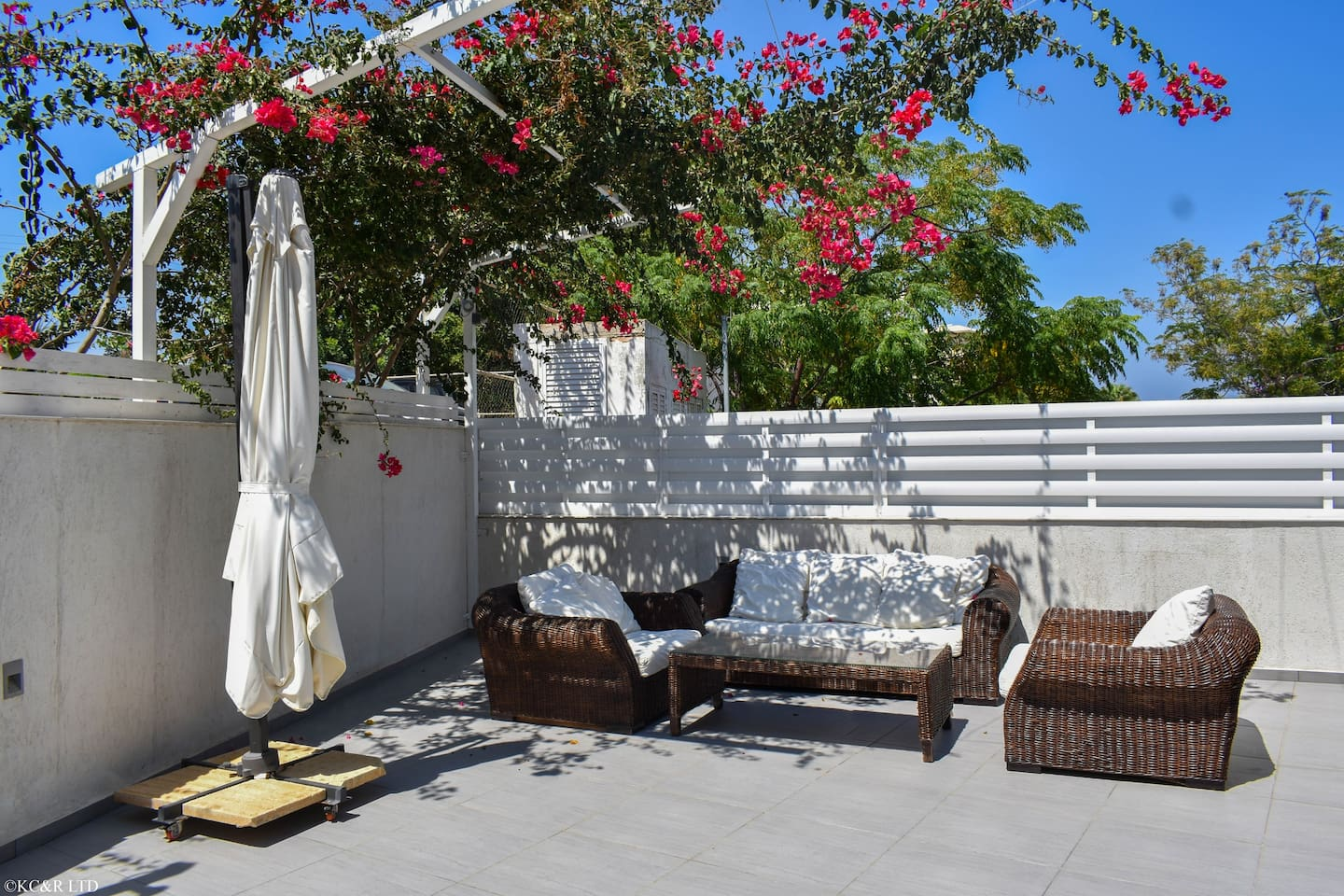 Front lounge area with bougainvillea pergola and shade umbrella