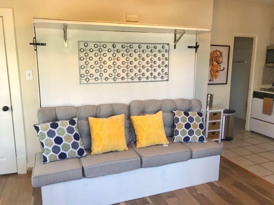 The sofa opens up to a full size queen bed that is mounted to the wall