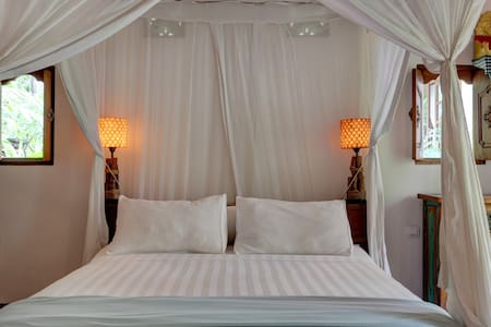 Queensize bed with crisp white cotton sheets and cotton mosquito net.
