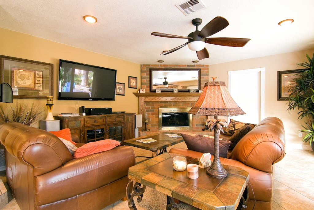 """60"""" plasma T.V. with surround stereo system and a large fireplace"""