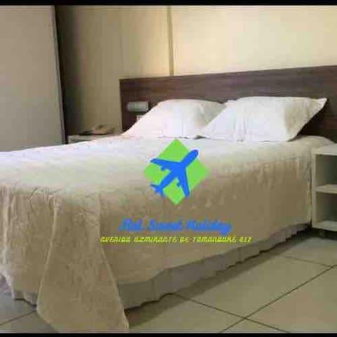 Quarto com cama de casal , armário embutido, mesas de cabiceira.