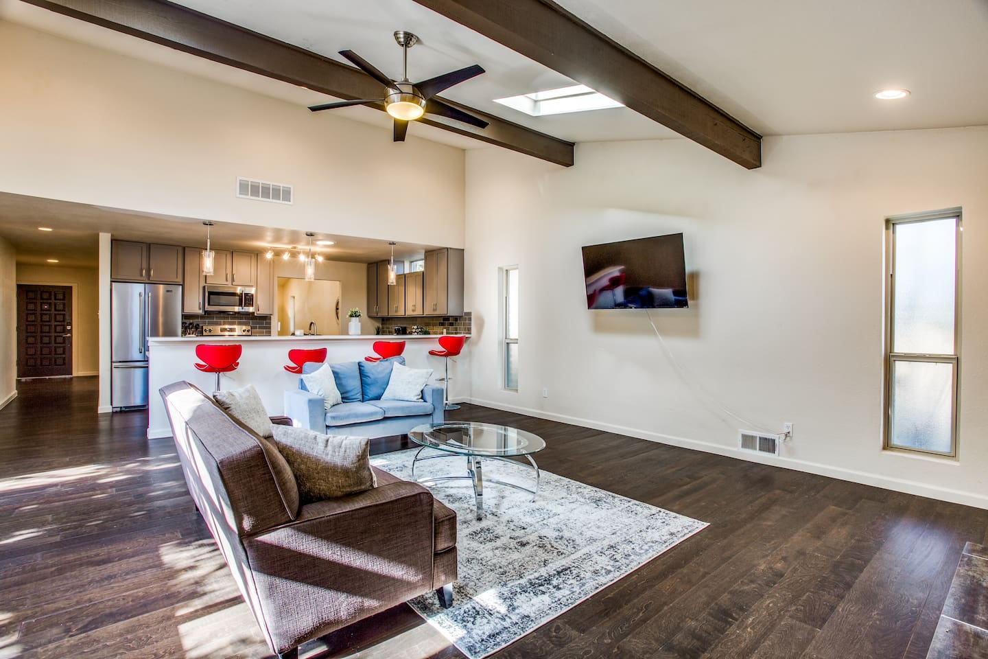 Large living area with open concept to kitchen, gas fireplace, flat screen tv and access to private patio.