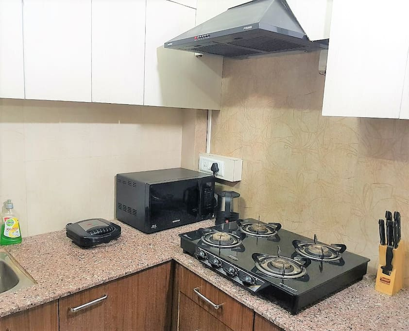 Fully loaded Kitchen with Stovetop, Gas, Refrigerator, Microwave, Cookware, Crockery, etc to make a complete meal.