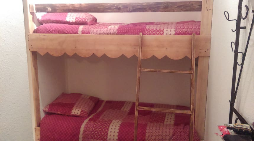 Deux lits superposés une place situés dans le couloir d'entrée de l appartement.