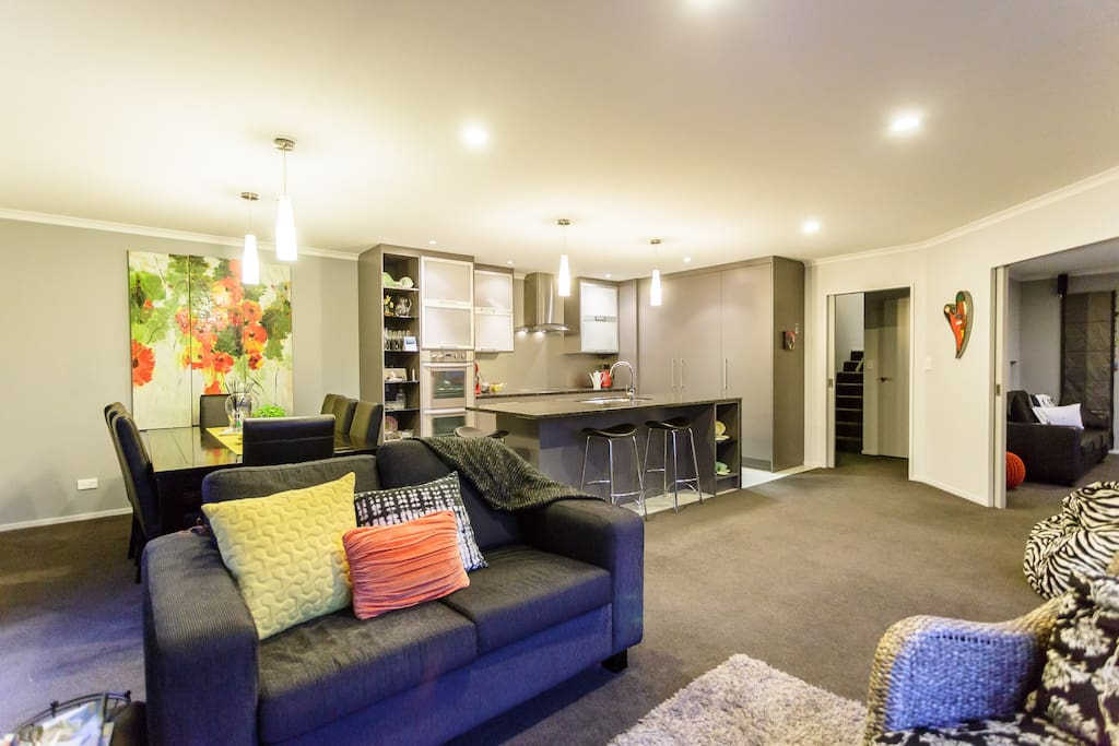 Open plan kitchen, dining and informal living area, with TV, heat pump.