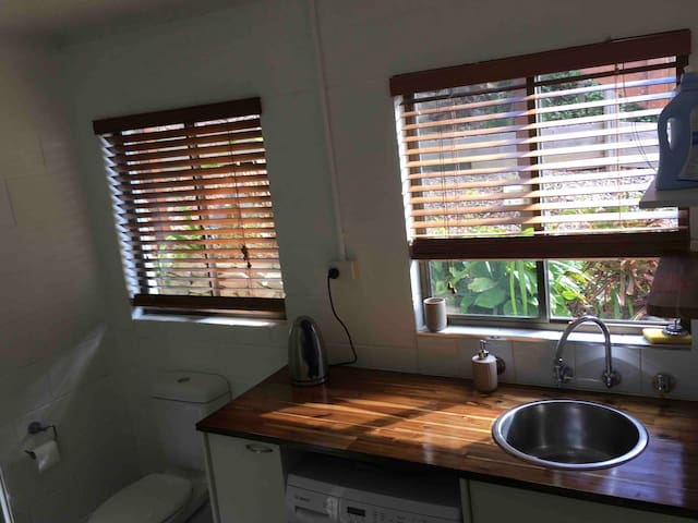 Bathroom with nice garden view, newly-varnished benchtop