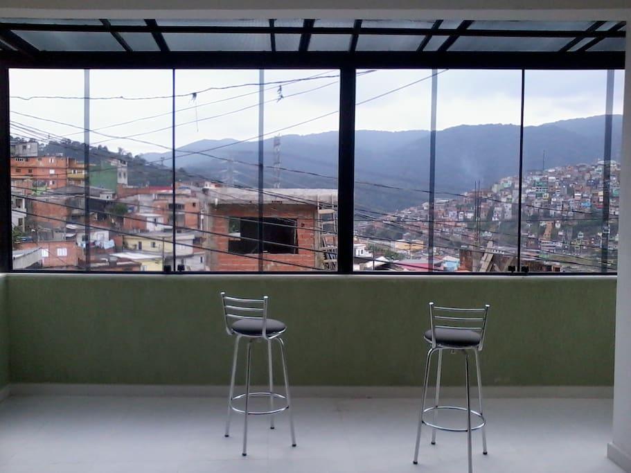 Sala de estar com vista panorâmica fechada em vidros fumês.
