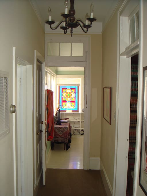 Photo of hallway. Kitchen and bathroom are to the left, two bedrooms to the right and living/sun room is straight ahead. The hammock in doorway can be strung across the room to an awaiting hook for an afternoon nap!