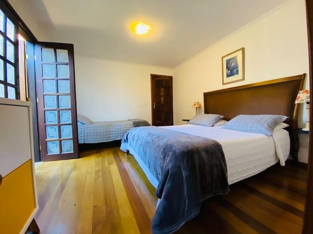 Suíte térrea com uma cama queen e uma cama de solteiro
