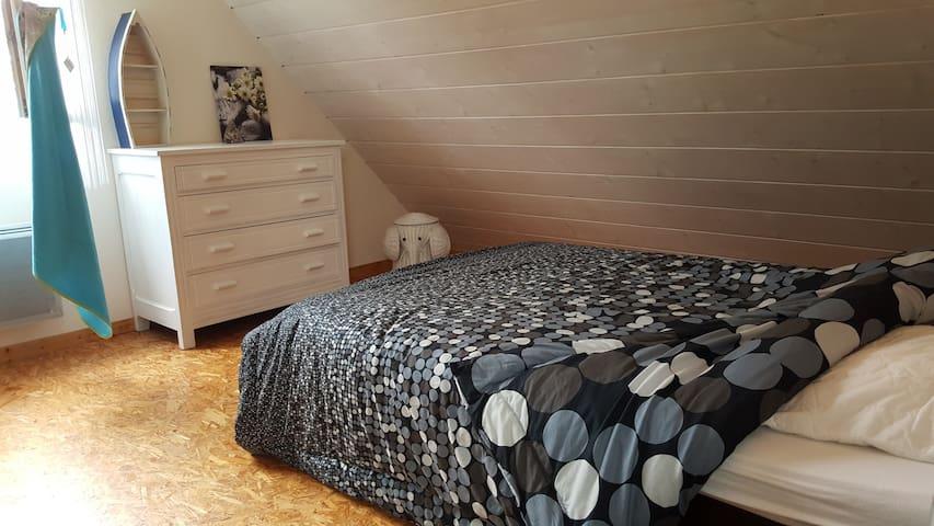 Chambre de l'étage avec lit double et lit bébé.