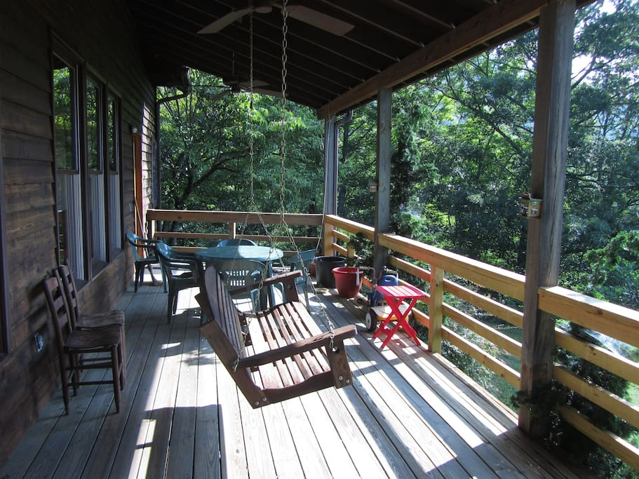 Swing and tables for outdoor dining. The hammock is back up at the end of the deck.