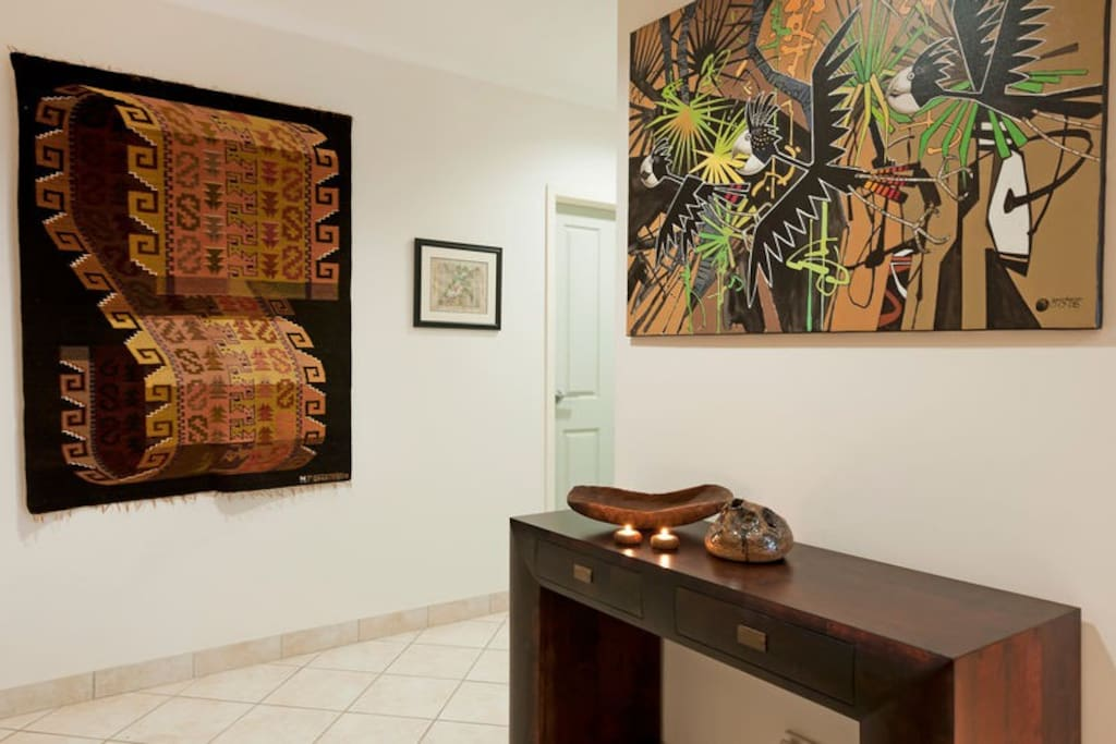 An eclectic artwork collection greets you in the entry area