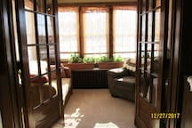 French doors lead from living room to sunroom