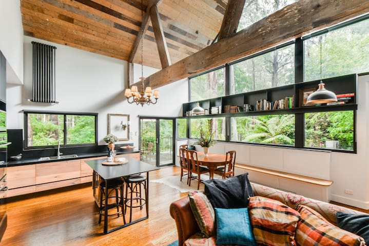 Living room, kitchen, dining area, doors onto front deck which looks into forest, beautiful for morning breakfast, dining table and banquette seating can accommodate a larger group with the addition of another dining table (available)
