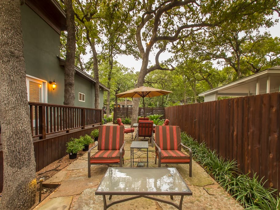 Lounge seating outdoors with trees canopying the yard.