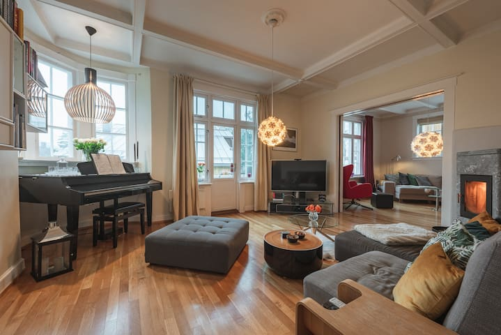 Lounge with a TV, game consoles, grand piano, balcony and fire place.