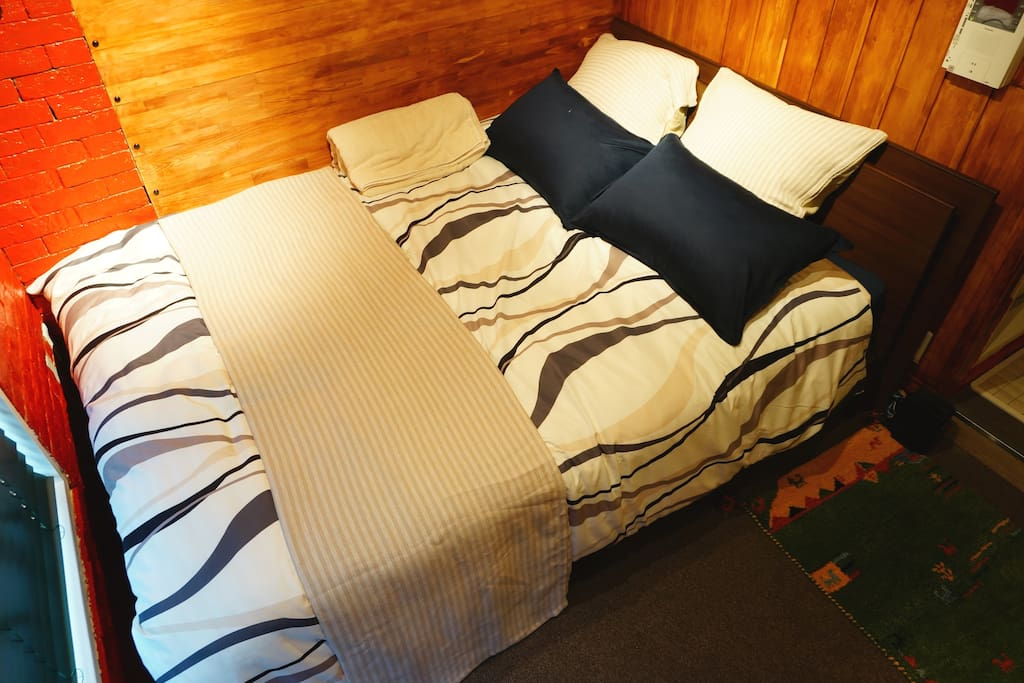 Comfortable double bed is in room.