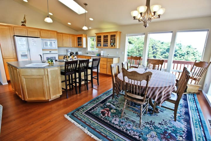 Fully equipped kitchen with all appliances, large prep island with sink, breakfast bar for three, and dining table for eight with spectacular ocean views and a door leading out to wrap around deck.